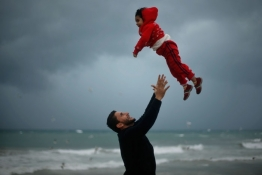 A Palestinian man plays with his daughter on a stormy day at a beach in Gaza City.