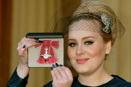 British singer Adele Adkins shows off her MBE for services to music presented to her by the Prince of Wales.