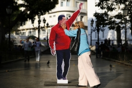 A woman touches a cardboard cut-out of late Venezuela's president Hugo Chavez at Plaza Bolivar in Caracas.
