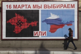A woman walking by a poster calling people to vote in the upcoming referendum, in the Crimean port city of Sevastopol.