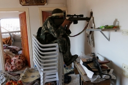 A rebel fighter sits on chairs as he aims his weapon through a hole inside a house in the town of Morek in Syrian Hama province.
