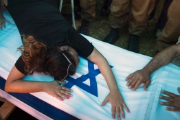 The mother of Israeli soldier Tal Yifrah mourns over her son's flag-covered coffin during his funeral in Rishon Lezion near Tel Aviv.