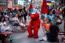 Jorge, an immigrant from Mexico, dressed as the Sesame Street character Elmo rests in Times Square, New York.